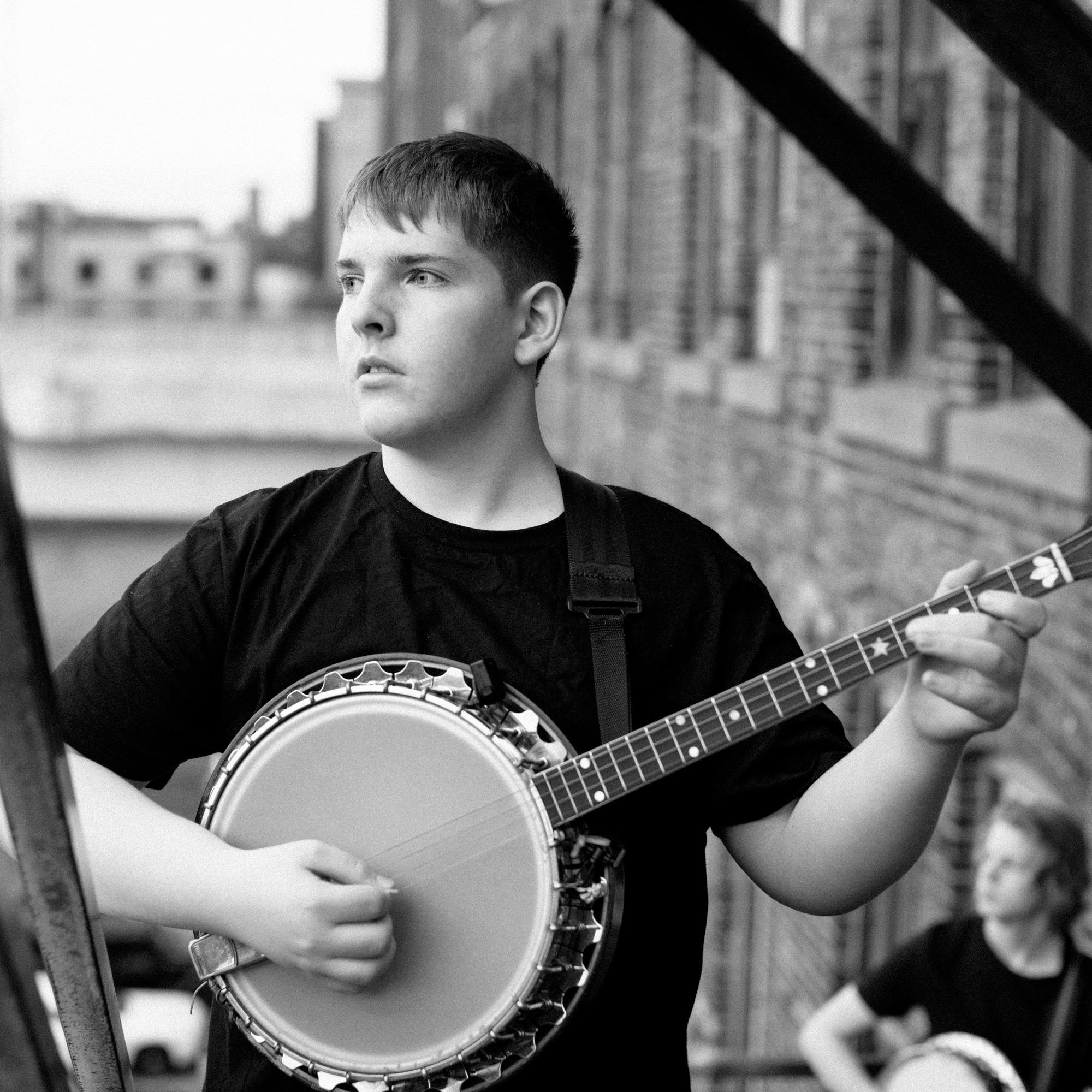 Promo image of Derek Anderson playing banjo